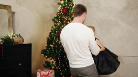Slowmotion shot of young father holding hands of his daughter and spinning her around at home by the Christmas tree stock video