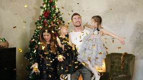 Slowmotion shot of young happy family of four by the Christmas tree throwing up golden confetti. Cute mother, father and. Two daughters celebrating Christmas stock footage
