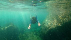 Slowmotion shot of a young man snorkeling and diving dip into sea. Showing ok under water.  stock video footage