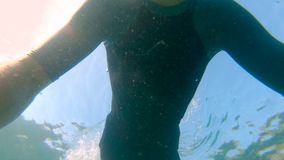 Slowmotion shot of a young man snorkeling and diving dip into sea. U.P.F 50 on a sleeve of a shirt - indicates. Ultraviolet Protection Factor of a shirt stock footage