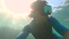 Slowmotion shot of a young man snorkeling and diving dip into sea. U.P.F 50 on a sleeve of a shirt - indicates. Ultraviolet Protection Factor of a shirt stock video