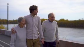 Slowmotion shot of a young man walking with his grandparents on a walkway along a riverside stock video