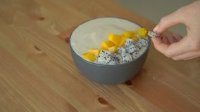 Slowmotion shot of a young woman cooking banana smoothie bowl with dragon fruit, mango, granola, raisin, almond slices. And chia seeds stock video