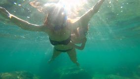Slowmotion shot of a young woman and her little son snorkeling in a sea.  stock video