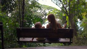 Slowmotion shot of young woman and her son swinging on a swings in a tropical garden.  stock video footage