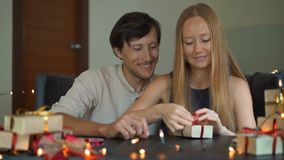 Slowmotion shot of a young woman and man father and mother wrap presents. Presents wrapped in craft paper with a red and. Gold ribbon for Christmas or new year stock footage