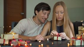 Slowmotion shot of a young woman and man father and mother wrap presents. Presents wrapped in craft paper with a red and. Gold ribbon for Christmas or new year stock video footage
