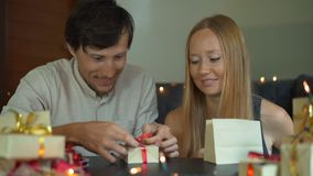 Slowmotion shot of a young woman and man father and mother wrap presents. Presents wrapped in craft paper with a red and. Gold ribbon for Christmas or new year stock video