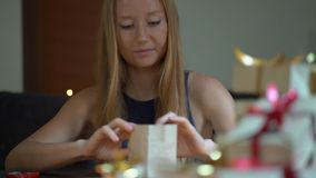 Slowmotion shot of a young woman is packing presents. Present wrapped in craft paper with a red and gold ribbon for. Christmas or new year. Woman makes an stock video footage