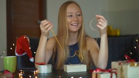 Slowmotion shot of a young woman is packing presents. Present wrapped in craft paper with a red and gold ribbon for. Christmas or new year. Woman makes an stock footage