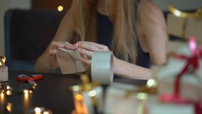 Slowmotion shot of a young woman is packing presents. Present wrapped in craft paper with a red and gold ribbon for. Christmas or new year. Woman makes an stock video