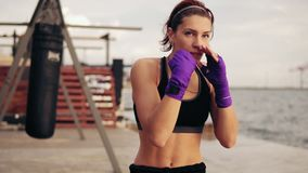 Slowmotion shot: young woman shadow boxing with her hands wrapped in purple boxing tapes looking in the camera stock video