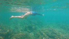 Slowmotion shot of a young woman snorkeling and diving in a beautiful sea.  stock video footage