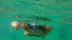 Slowmotion shot of a young woman snorkeling and having fun in a sea.  stock footage