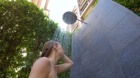 Slowmotion shot of a young woman takes a shower in a tropical garden. Holidays in a tropical resort concept. Young woman stock video