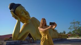 Slowmotion shot of a young woman traveler visiting the the Wat Srisoonthorn temple with a statue of the lying Buddha on stock footage