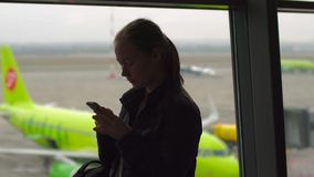 Slowmotion shot of a young woman using a smartphone in front of a big window at an airport.  stock video footage