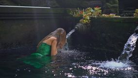 Slowmotion shot of a young woman visiting the holly springs in Indonesia. Tirta Empul holy water springs on the Bali