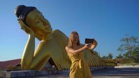 Slowmotion skott av en handelsresande f?r ung kvinna som bes?ker p? den Wat Srisoonthorn templet med en staty av den liggande Bud arkivfilmer