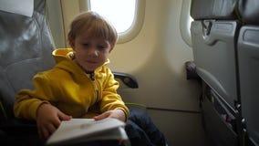 Slowmotion skott av en pojke i gult omslag ombord av ett flygplan som läser en säkerhetsanvisning stock video