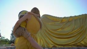Slowmotion skott av en ung kvinna och hennes lilla son som har roligt framme av en staty av den liggande Buddha p? den Phuket ?n arkivfilmer