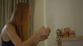 Slowmotion skott av en ung kvinna som förbereder en edvent kalender för jul stock video