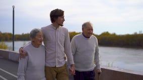 Slowmotion skott av en ung man som går med hans morföräldrar på en gångbana längs en flodstrand stock video