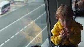 Slowmotion skott av en ung pojke i ett gult omslag som äter en kaka som framme sittting av ett stort fönster på en flygplats stock video