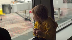 Slowmotion skott av en ung pojke i ett gult omslag som äter en kaka som framme sittting av ett stort fönster på en flygplats arkivfilmer