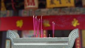 Slowmotion skott av röka aromatiska pinnar i en rökelsekar inom av en buddistisk tempel arkivfilmer