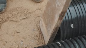 Slowmotion sledgehammer hitting piece of wood stuck to black plastic pipe stock video