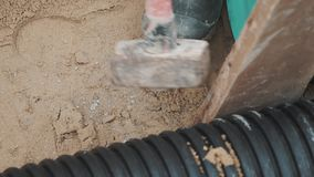 Slowmotion sledgehammer hitting piece of wood stuck between two plastic pipe stock video footage