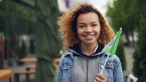 Slowmotion stående av den lyckliga turisten för afrikansk amerikankvinna som ser kameran, ler och rymmer den brasilianska flaggan stock video