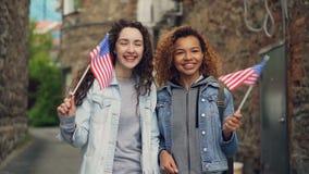 Slowmotion stående av två nätta flickor i vinkande amerikanska flaggan för tillfälliga kläder och att skratta se kameran lager videofilmer