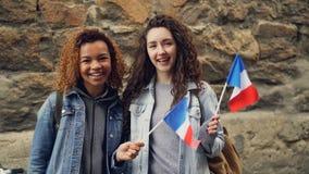 Slowmotion stående av två skratta kvinnastudenter som vinkar franskaflaggor och ser kameraanseende mot brickwall stock video