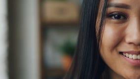 Slowmotion stående för närbild av den halva framsidan för snygg asiatisk dam med det mörka ögat, härlig hud med smink och vit lager videofilmer