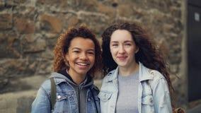 Slowmotion stående för närbild av två lyckliga studenter afrikansk amerikan och Caucasian seende kamera och skratta blandat arkivfilmer