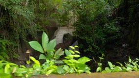 Slowmotion steadicam schoss von einem tropischen Fluss durch den Pura Gunung Lebah-Tempel in Ubud auf der Bali-Insel stock footage