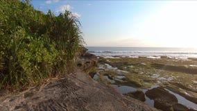 Slowmotion steadicam schoss von einer Familie, die auf eine felsige K?ste auf einen Tanah-Lostempel auf der Bali-Insel geht stock footage