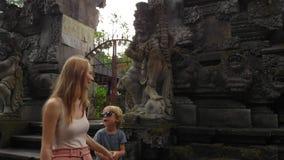 Slowmotion steadicam schoss von junge Frau und Hel littl Sohn, der um den Pura Gunung Lebah-Tempel in Ubud auf geht stock video