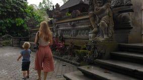 Slowmotion steadicam schoss von junge Frau und Hel littl Sohn, der um den Pura Gunung Lebah-Tempel in Ubud auf geht stock video footage
