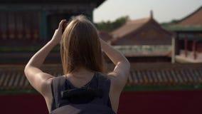 Slowmotion Steadicam skott av en loppbloger för ung kvinna som besöker Forbiddenet City - forntida slott av Kina kejsare arkivfilmer
