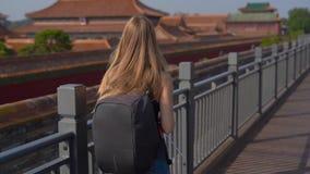 Slowmotion Steadicam skott av en loppbloger för ung kvinna som besöker Forbiddenet City - forntida slott av Kina kejsare lager videofilmer