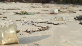 Slowmotion steadycam shot of a beach with fine white sand covered with garbage.  stock video