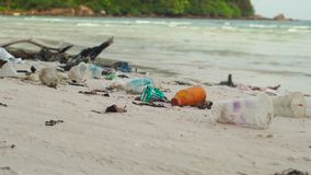 Slowmotion steadycam shot of a beach with fine white sand covered with garbage.  stock video footage
