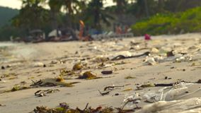 Slowmotion steadycamschot van een strand met fijn wit die zand met huisvuil wordt behandeld stock videobeelden