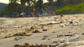 Slowmotion steadycamskott av en strand med fin vit sand som täckas med avskräde lager videofilmer