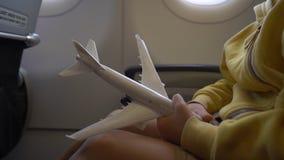 Slowmotion strzał chłopiec która bawić się z biel zabawki samolotowym obsiadaniem w krześle na samolocie troszkę Wolność zbiory