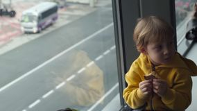 Slowmotion strzał młoda chłopiec je ciastko sittting przed dużym okno przy lotniskiem w żółtej kurtce zdjęcie wideo
