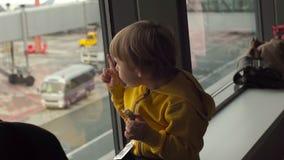Slowmotion strzał młoda chłopiec je ciastko sittting przed dużym okno przy lotniskiem w żółtej kurtce zbiory wideo